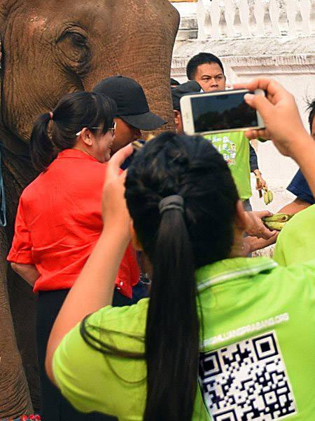 Femme prenant une photo avec son smartphone au Laos.