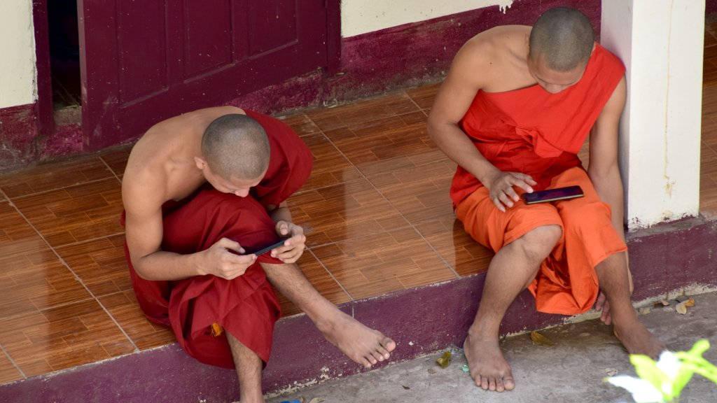Moines sur leur smartphone au Laos.