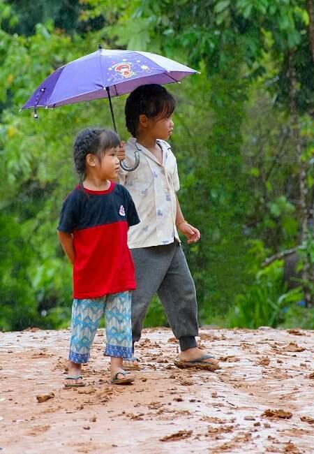 Fillettes sous la pluie au Laos.